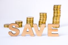 Word sparen van driedimensionele brieven is in voorgrond met de groeikolommen van muntstukken op vage achtergrond Sparen concept  royalty-vrije stock afbeeldingen