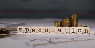 Word SPECULATION composed of wooden letter. Stacks of coins in the background. Closeup royalty free stock images