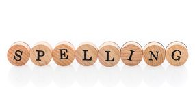 Word Spelling from circular wooden tiles with letters children toy. royalty free stock image