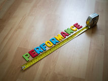 """Word spelling """"Performance"""" and yellow measuring tape on wooden floor background. Performance measurement concept Stock Photography"""