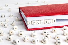 Word Sponsor written in wooden blocks in red notebook on white w. Ooden table. Wooden abc Royalty Free Stock Photography