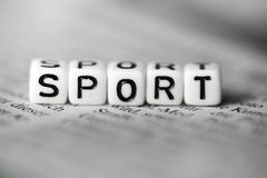 Word SPORT formed by wood alphabet blocks on newspaper. Closeup Stock Photos