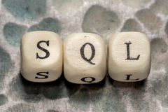 The word sql. Structured query language, lined with wooden blocks on a metal forged textural background Royalty Free Stock Image