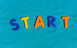 The word Start composed from letters. The word Start composed from colorful children toy big letters on the grass royalty free stock photo