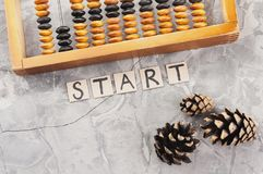 Word START laid out of handwritten letters on cardboard squares near old wooden abacus and three cones. On gray cracked concrete stock images