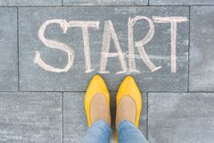 Word Start On The Asphalt And Feet Woman Stock Photography
