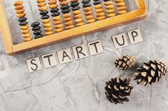Word START UP laid out of handwritten letters on cardboard squares near old wooden abacus and three cones. On gray cracked concrete stock images