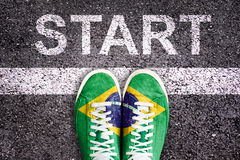 Word Start written on an asphalt road with legs and shoes colored with brazilian flag Royalty Free Stock Image