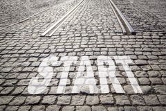 Word START is written on cobbled paved road with rails - beginning of road, new life. royalty free stock photo