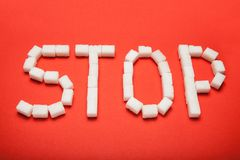 The word `stop` from cubes of sugar on a red background. royalty free stock images