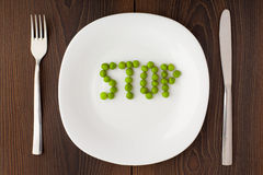 Word stop made of peas on a plate Stock Images
