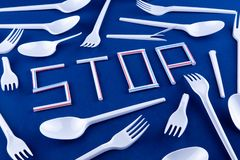 The word stop made of plastic tubes on a blue background with plastic utensils environmental pollution concept. Top view.  stock photos
