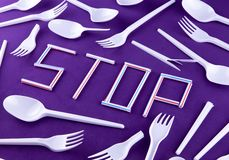 The word stop made of plastic tubes on a purple background with plastic utensils environmental pollution concept. Top view.  stock photo