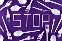 The word stop made of plastic tubes on a purple background with plastic utensils environmental pollution concept. Top view.  royalty free stock photos