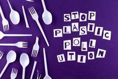 The word stop plastic pollution made of cut paper on a purple background with plastic utensils environmental pollution concept. Top view stock photos