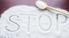The word STOP written on a covered sugar and a wooden spoon on the table stock images