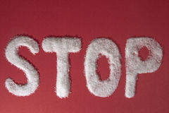 The word STOP written by sugar grains on red background royalty free stock photo