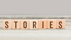 Word Stories on wood cubes. Word Stories on wood cube dices on aged table Stock Image
