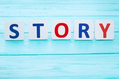 Word story on blue wooden table. Selective focus and copy space royalty free stock image