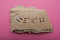 The word `stress` written on an old torn cardboard is isolated on a pink background. stock photos