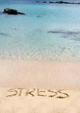 Word Stress written on sand, washed away by waves, relax concept Royalty Free Stock Photo