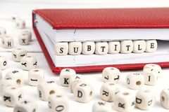 Word Subtitle written in wooden blocks in red notebook on white Royalty Free Stock Photography