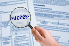 Word Success, magnifying glass in hand Stock Photos