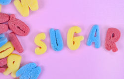 Word Sugar on pink table Royalty Free Stock Photo