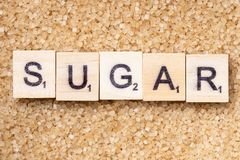 Word `azucar` on scrabble uppercase letters. Full frame Word `azucar` on scrabble uppercase letters over a brown sugar surface stock images