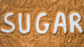 The word sugar written over a pile of brown sugar Stock Image