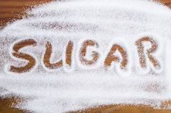 The word sugar written into a pile of white granulated sugar Royalty Free Stock Photo