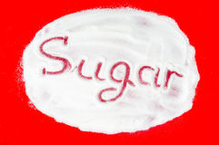 Word sugar written into a pile of white granulated sugar Stock Photography