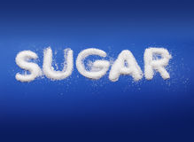 Sugar. Word Sugar written with real fine granulated sugar on blue background Royalty Free Stock Photography