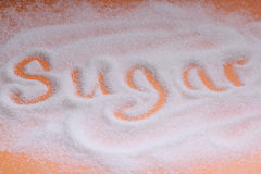 The word Sugar written in sugar grains. Overhead view. Stock Photos