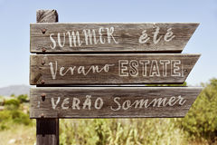 Word summer in different languages in a signpost. Closeup of a rustic wooden signpost in a natural landscape with the word summer written in english, french Royalty Free Stock Photography