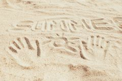 Word summer and hand prints on sand. Inscription word summer and hand prints with drawing sun on sand, concept of vacations royalty free stock photography