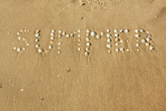 Word summer laid out seashells on the sand Royalty Free Stock Photos