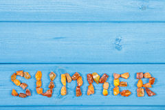 Word summer made of amber stones on blue boards, summer time, copy space for text Royalty Free Stock Photo