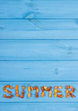 Word summer made of amber stones on blue boards, summer time, copy space for text Royalty Free Stock Image