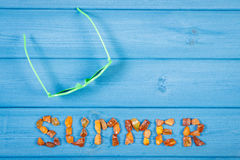 Word summer made of amber stones and sunglasses on blue boards, summer time, copy space for text Stock Photo