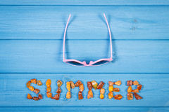 Word summer made of amber stones and sunglasses on blue boards, summer time Royalty Free Stock Image