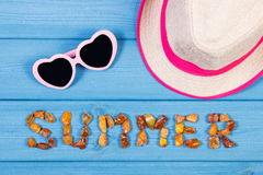 Word summer made of amber stones, sunglasses and straw hat on blue boards, summer time Royalty Free Stock Photo