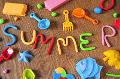 Word summer made from modelling clay. The word summer made from modelling clay of different colors and some beach toys such as toy shovels and sand moulds, on a royalty free stock photography