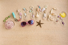 Word summer made from sea shells, on sand Stock Image