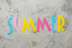 Word summer of paper multicolored letters on a light concrete background. summer. vacation. relaxation. top view. Word summer of paper multicolored letters on a stock photos