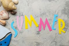 The word summer from paper with multicolored letters and sea accessories, shells on a light concrete background. summer. vacation. Relaxation. top view stock image