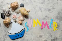 The word summer from paper with multicolored letters and sea accessories, shells on a light concrete background. summer. vacation. Relaxation. top view royalty free stock photos