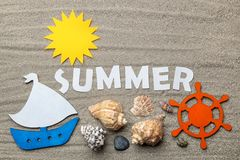 The word summer of paper white letters and summer and sea accessories on the sea sand. summer. vacation. relaxation. top view royalty free stock photography