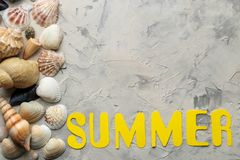 The word summer of paper yellow letters and sea accessories, shells on a light concrete background. summer. vacation. relaxation. Top view. space for text royalty free stock image