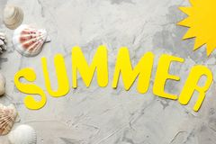 The word summer of paper yellow letters and sea accessories, shells on a light concrete background. summer. vacation. relaxation. Top view stock image
